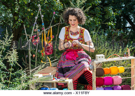 Button maker, young woman in colorful dirndl with Posamentenknopf Collier siting in garden and working on Posamentenknopf - Stock Photo