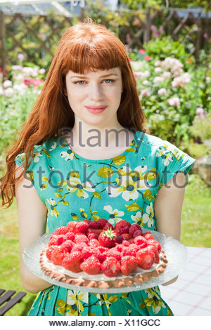 young woman holding strawberry tart. - Stock Photo