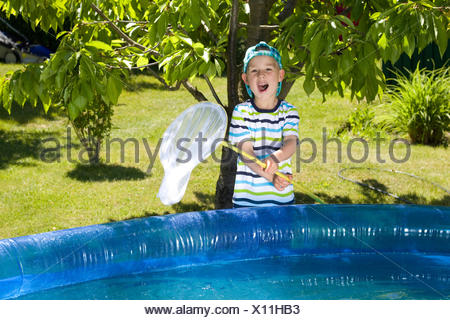 little boy maintains the pool - Stock Photo