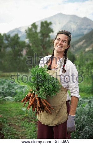 Portrait of woman holding carrots in field - Stock Photo