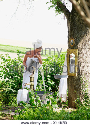 Woman taking a bath in a garden, Sweden. - Stock Photo