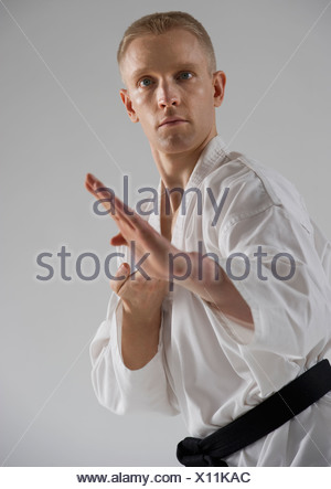 Young man performing karate stance on white background - Stock Photo