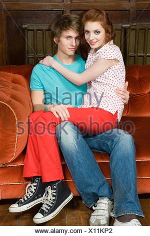 Teenage couple sitting on sofa - Stock Photo