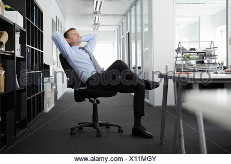 Mature businessman leaning back in office chair - Stock Photo