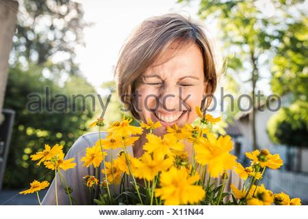 Portrait of mature woman with yellow flowers - Stock Photo