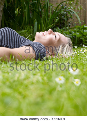 Smiling woman laying in grass - Stock Photo