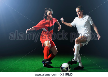 Two female soccer players tackling ball - Stock Photo