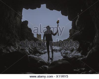 Man With Flaming Torch Walking In Cave - Stock Photo