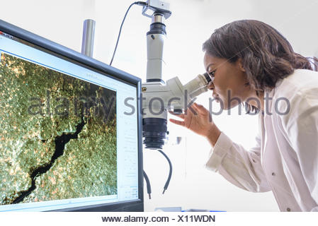 Scientist inspecting metal surface with microscope in laboratory - Stock Photo