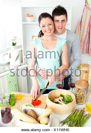 Enamored young couple cutting vegetables in the kitchen - Stock Photo