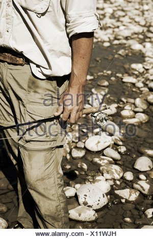 A fisherman holds his fly fishing rod on his side with white river rocks behind him. - Stock Photo