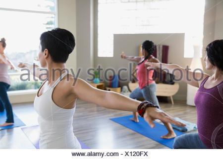 Women practicing warrior 2 pose in yoga class - Stock Photo