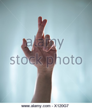 Close up of hand with crossed fingers - Stock Photo
