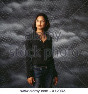Woman standing in rainstorm - Stock Photo