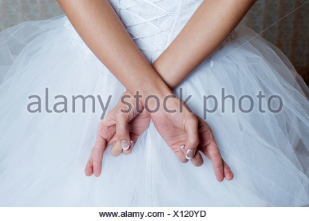 Brides fingers crossed behind back, mid section - Stock Photo