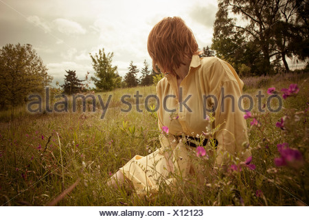 Young woman sitting in field, looking away - Stock Photo