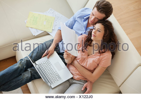 Couple sitting sofa paying bills together - Stock Photo