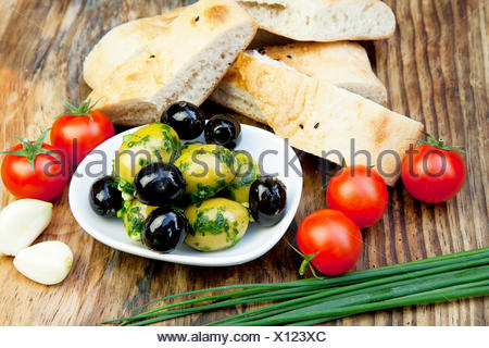 green olives with fresh bread and herbs on a holzbret - Stock Photo