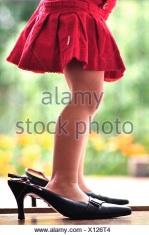 Legs of girl (2-3) in high heels - Stock Photo