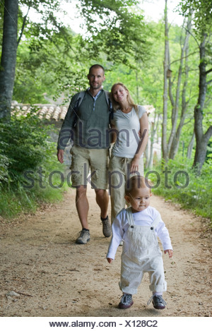Toddler girl walking in woods with parents - Stock Photo