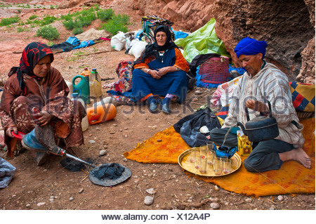 Nomadic cave-dwellers, Berber, a man wearing a blue turban is pouring a cup of tea, a woman is using bellows to keep the - Stock Photo
