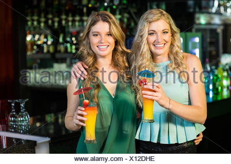 Happy friends drinking cocktails - Stock Photo