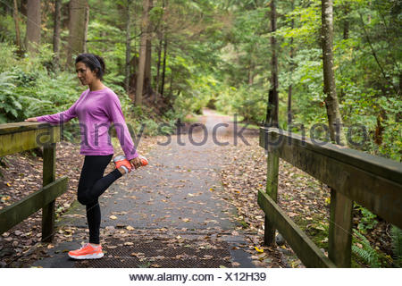Woman stretching leg preparing for run in woods - Stock Photo