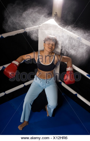 Young woman resting at a corner of a boxing ring - Stock Photo
