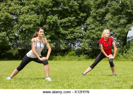 Women warming up for exercise in park - Stock Photo