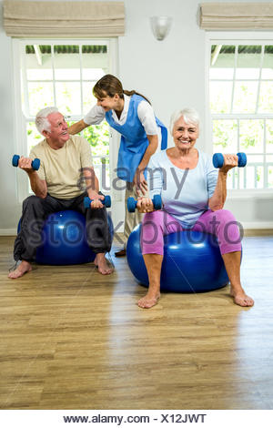 Senior man and woman holding dumbbellls - Stock Photo