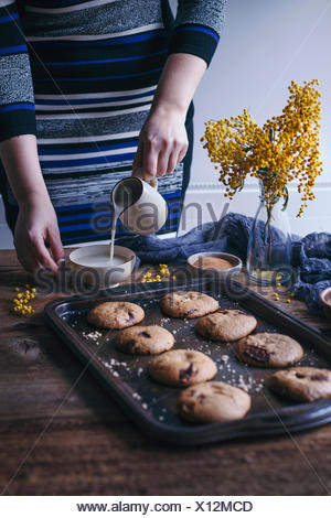 Woman pouring almond milk in a cup and hazelnut chocolate chip cookies on a baking tray - Stock Photo