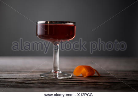 Sophisticated cocktail in a vintage, silver lined, coupe glass with orange peel on a rustic, gray wood surface. - Stock Photo