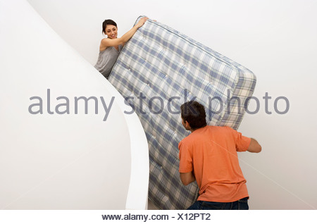 Couple moving house carrying king size matress on staircase smiling - Stock Photo