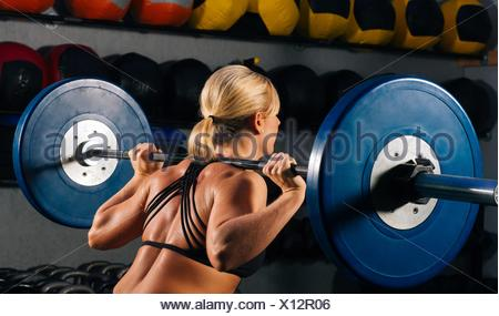 Young woman squatting with barbell on shoulders in gym - Stock Photo