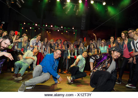 Crowd watching and cheering break dancers - Stock Photo