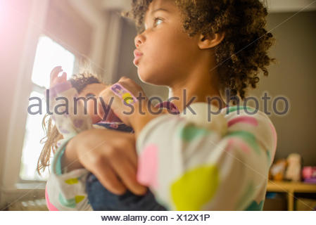 Close up of girl carrying and feeding doll - Stock Photo