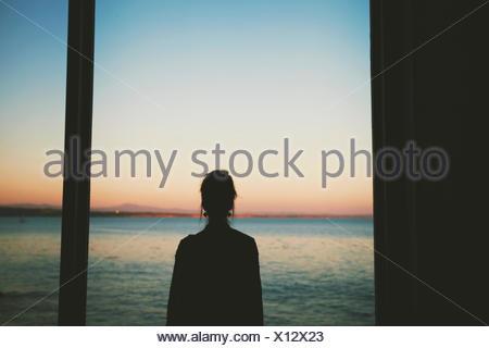 Woman looking at sea through window - Stock Photo