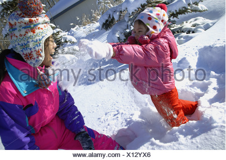 Mother and Daughter having a snowball fight - Stock Photo
