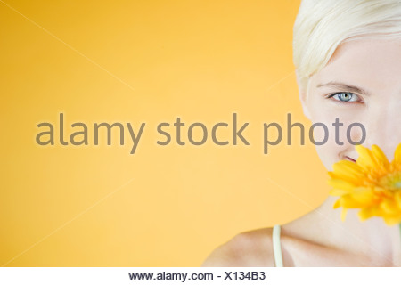 A Young Woman With An Orange Flower - Stock Photo