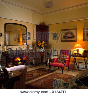 Large mirror above fireplace with lighted fire in yellow living room - Stock Photo