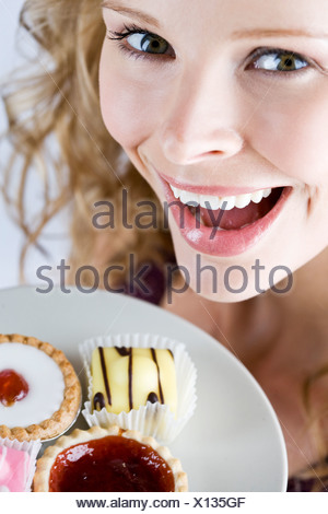 A portrait of a young blonde woman holding a plate of assorted cakes, close-up - Stock Photo