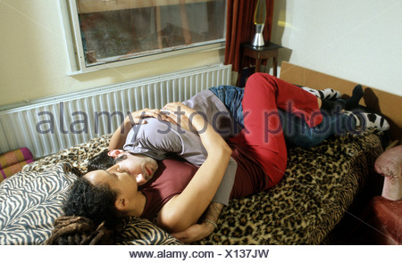 Couple in bed hug hugging - Stock Photo