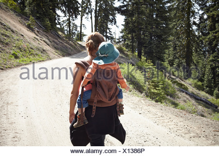 Rear view of mother carrying toddler in baby carrier - Stock Photo