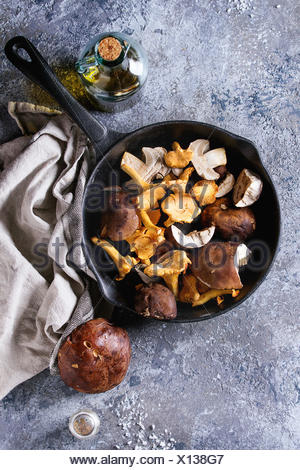 Heap of fresh forest porcini boletus and chanterelles mushrooms in iron cast pan with olive oil and salt, served won textile napkin with knife over gr - Stock Photo