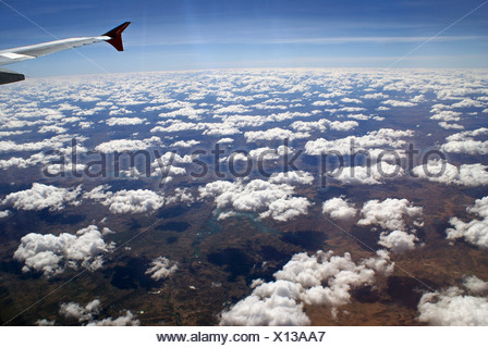 Cumulus clouds, seen from the window of an airplane - Stock Photo