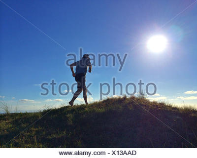 Man running up a sand dune on the beach, Denmark - Stock Photo