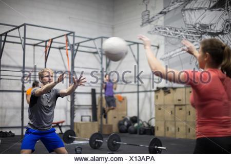 Man throwing medicine ball towards woman in crossfit gym