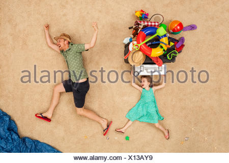 Father and daughter running to the sea, carrying beach equipment on the head - Stock Photo