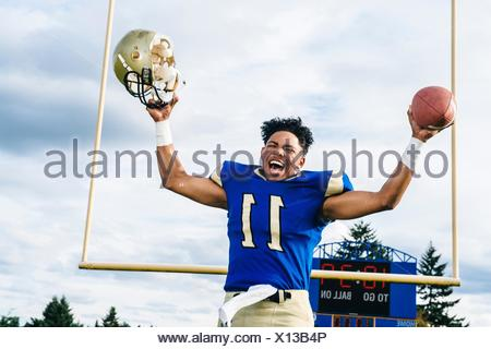 Teenage American football player celebrating victory on soccer pitch - Stock Photo