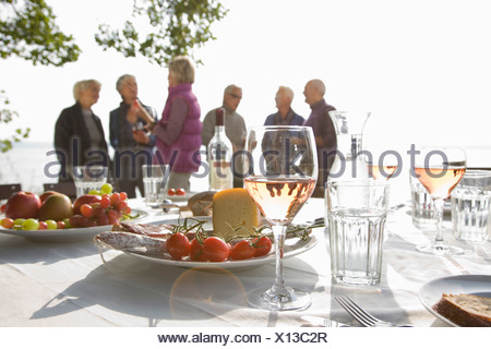Six senior friend talking behind a table laid for lunch - Stock Photo
